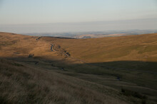 Sunset Over The Brecon Beacons With A Narrow Road Down A Valley