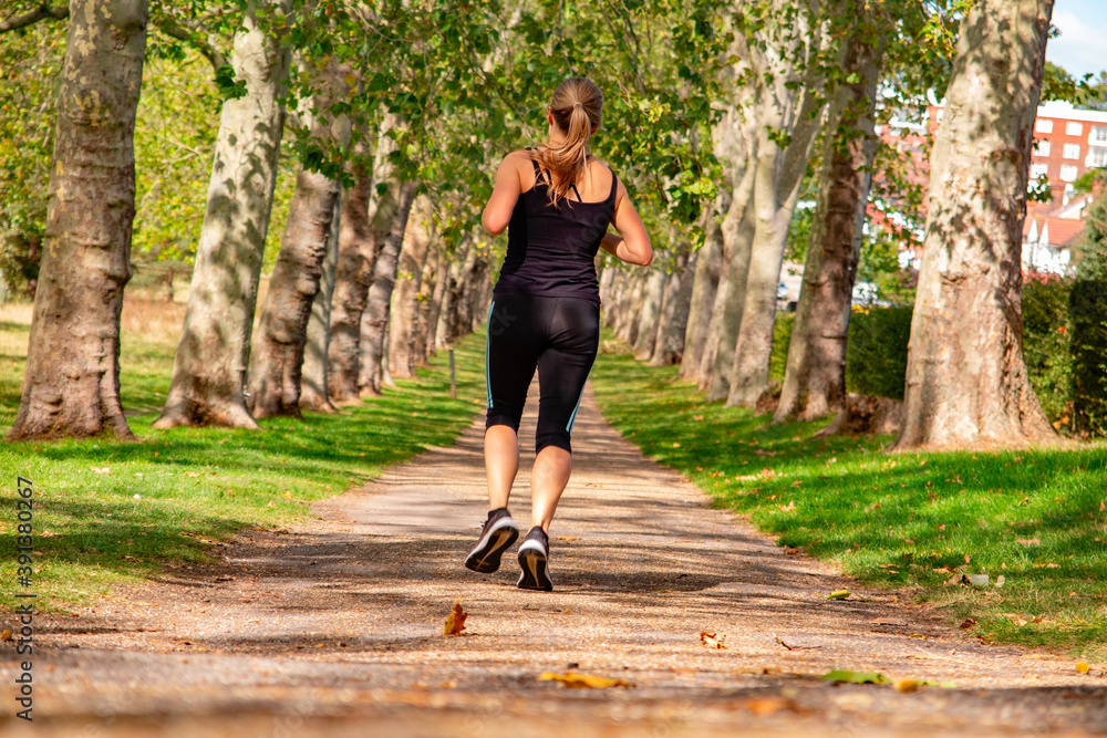 Fototapeta parco pubblico, corridore donna in completo nero di spalle, Dollis Hill, Gladstone Park