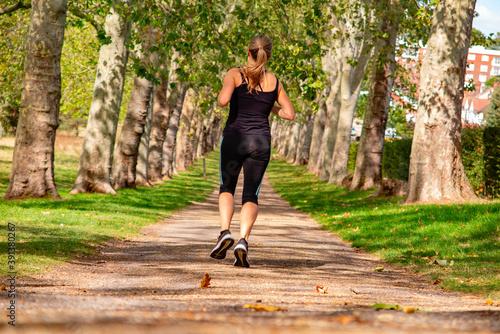 Tela parco pubblico, corridore donna in completo nero di spalle, Dollis Hill, Gladsto