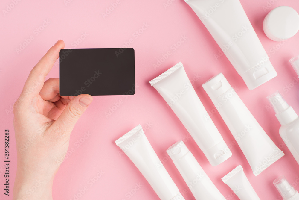 Fototapeta Cosmetics shop voucher concept. Top above overhead pov first person view photo of female hand holding voucher isolated on pink pastel background with white cream tubes