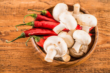 White Mashrooms And Red Hot Chilli Peppers In Wooden Natural Dish Plate For Cooking On Old Retro Vintage Aged Wood Board Texture