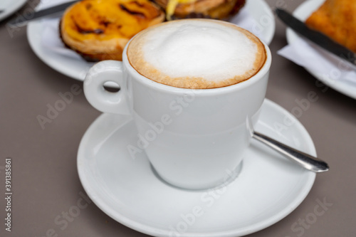Tela Cup of cappuccino coffee served with traditional dessert pastry in Portugal, nat