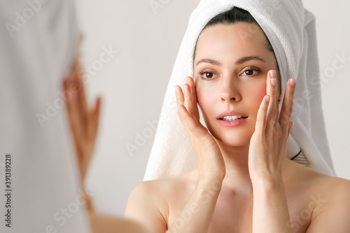 A natural woman with good skin holds her cheeks and looks in the mirror. SPA, cosmetology, beauty