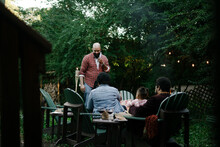 Friends Gathered For Evening Party In Backyard Around Firepit