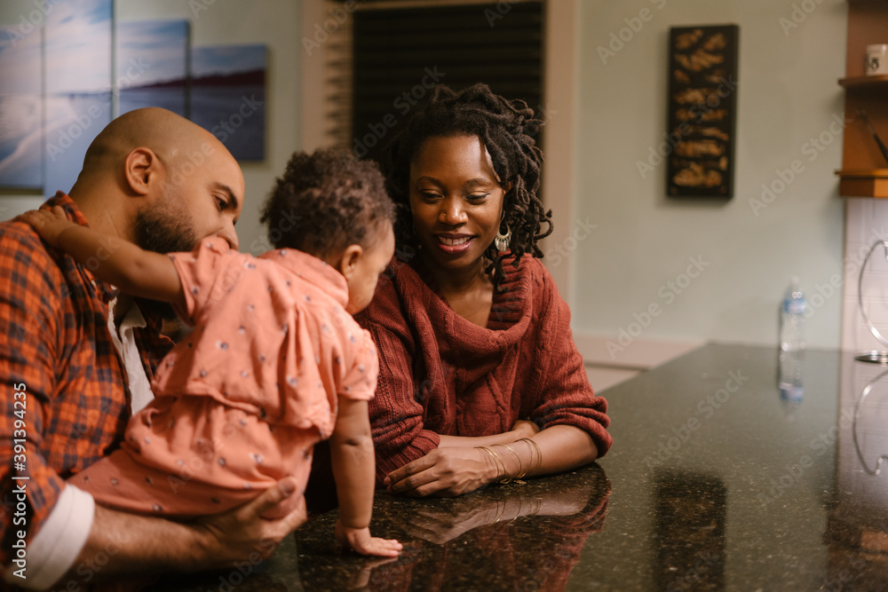 African American mom and dad spending quality time with daughter at home