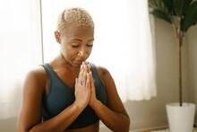 Black Woman Meditating At Home