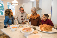 Family Prepares Thanksgiving Food In Kitchen