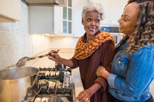 Black Mother And Daughter Cooking In The Kitchen