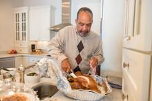 Black Granddad Preparing Turkey For Thanksgiving Dinner