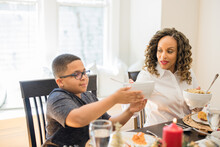 Black Family Eating Christmas Dinner Together At Dining Room Table
