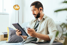 Young Bearded Man Working From Home. Man On Sofa At Home Using Digital Tablet
