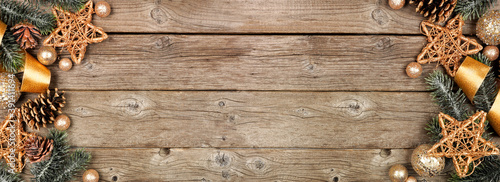 Obraz Christmas double border of gold ribbon and decor with tree branches. Overhead view on a rustic wood banner background. Copy space. - fototapety do salonu