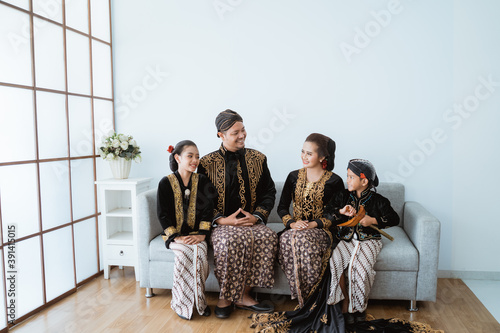 Fototapeta Portrait of a happy family wearing traditional Javanese clothes. concept of family photo Javanese traditional clothes in the living room obraz na płótnie