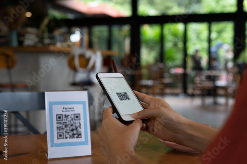 Fototapeta Woman is using a mobile phone to scan a QR coach to pay for food and drinks instead of cash in a coffee shop. QR code payment and cash technology concept. obraz
