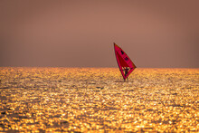 Silhouette Sportsman Is Windsurfing At Sunset Time On Wind Of Wave