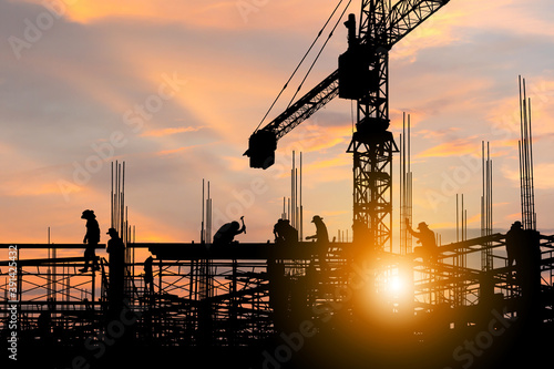 Obraz na plátně Silhouette of Engineer and worker checking project at building site background,