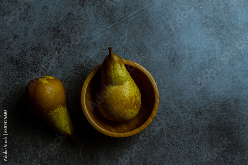 Top view of two pears, one in a wooden bowl, the other next to it on grungy blue Wallpaper Mural