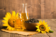 Closeup Photo Of Sunflower Oil With Seeds On Wooden Background. Bio And Organic Product Concept.