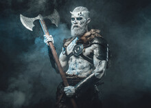 Risen From The Dead Northern Warrior With Horns And Pale Skin Holding His Two Handed Axe In Frosty Fog And Dark Background.