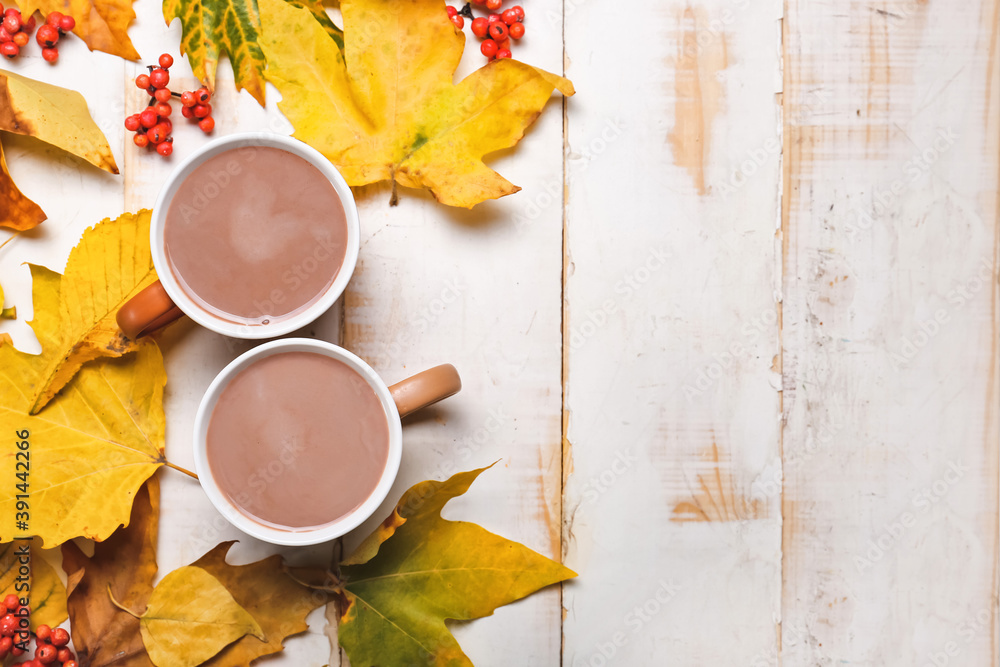 Fototapeta Cup of hot cacao drink with autumn leaves on white wooden background