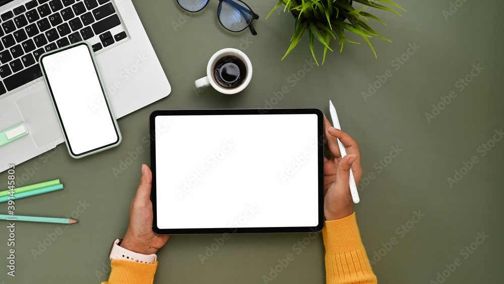 Fototapeta Over head shot of young woman in .yellow sweater hands holding tablet with white screen and stylus pen at her working desk.