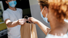 Cropped Shot Of Woman Wearing Mask Taking Paper Bag With Her Order From Hands Of Shop Assistant While Collecting Her Purchase From The Pickup Point During Coronavirus Lockdown