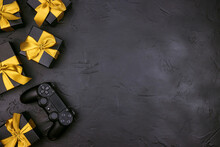 Black Background With Joystick Gaming Controller And Gift Boxes With Gold Ribbon.