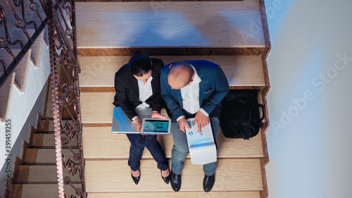 Top view of businesspeople doing overtime late night afterhours tired on a deadline using modern gadget Wallpaper Mural