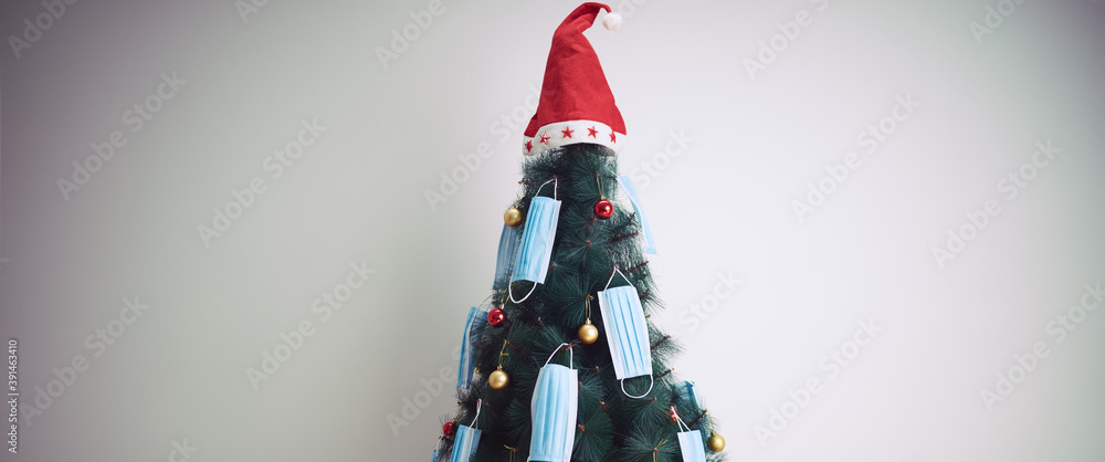 Fototapeta Christmas tree decorated with surgical masks - illustration to virus pandemic 2020 / 2021 social distance, lockdown and quarantine isolation.