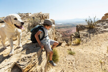 Young Boy Hiking With His Dog On Chimney Rock Trail, Through A Protected Canyon Landscape