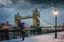 London Winter Concept With A Tourist Holding A British Flag Souvenir Umbrella Standing In Front Of The Tower Bridge During Evening Time With Snowfall And Cold Temperature, United Kingdom