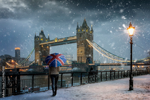 Obraz na plátně London winter concept with a tourist holding a british flag souvenir umbrella st
