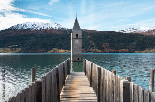 Canvastavla Famous submerged church steeple arising from the alpine Resia Lake, in the town of Curon Venosta, in the italian Dolomite region of Trentino Alto Adige