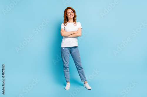 Obraz Photo portrait full body view of confident girl with crossed arms looking to side isolated on pastel blue colored background - fototapety do salonu