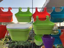 Closeup Of Colorful Plastic Planter Flowerpots With Hooks Hanging From A Rope At The Open-air Market