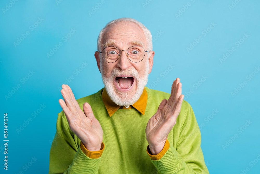 Fototapeta Photo of crazy retired granddad open mouth raise palms wear eyeglasses green pullover isolated blue color background