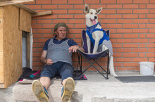 Two Homeless Fiends - Man And Dog Resting While Sitting On Favourite Places Eagainst Brick Wall