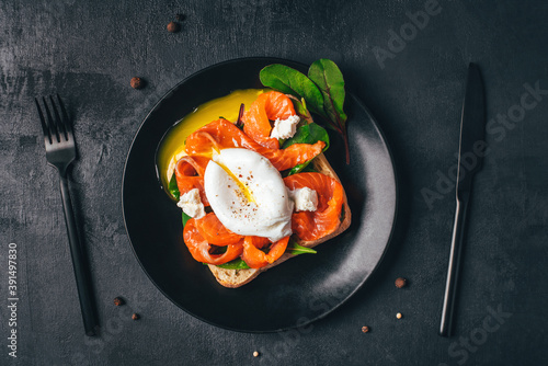 Sandwich with salmon, cheese, herbs and poached egg on black background фототапет