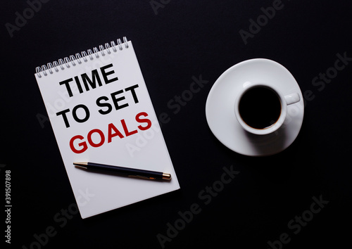 TIME TO SET GOALS is written in a white notebook in red type near a white cup of coffee on a black table. Motivational concept