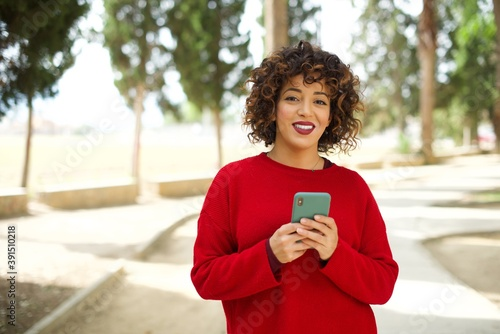 Fotomural Photo of Young beautiful Arab woman standing outdoors wearing red sweater enjoys distant communication, uses mobile phone, surfs fast unlimited internet, has pleasant smile makes shopping online
