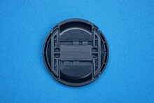 One Black Plastic Camera Lens Cap Lies On A Blue Table