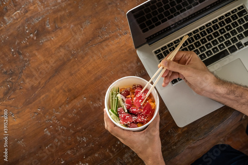 Fotografie, Obraz Busy young man in casual wear sitting at desk with a laptop at home or in the office and eating healthy takeout poke bowl food from container during lunch break