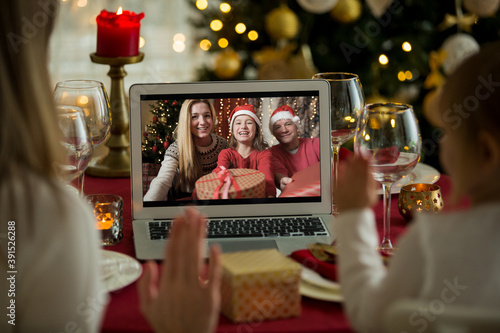 Obraz na plátne A happy family with a child is celebrating Christmas with their friends on video call using webcam