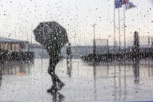 Selective Focus Shot Of A Wet Window With A View Of People With Umbrella Walking On A Rainy Day