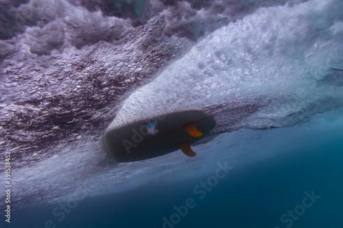 Under water view of wave, surfboard, underwater shot