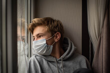 Young Ill Teenage Boy Looking Sad With Protective Mask At Home Behind Window In Quarantine And Lockdown Missing School And Freedom During Covid-19 Coronavirus Worldwide Pandemic