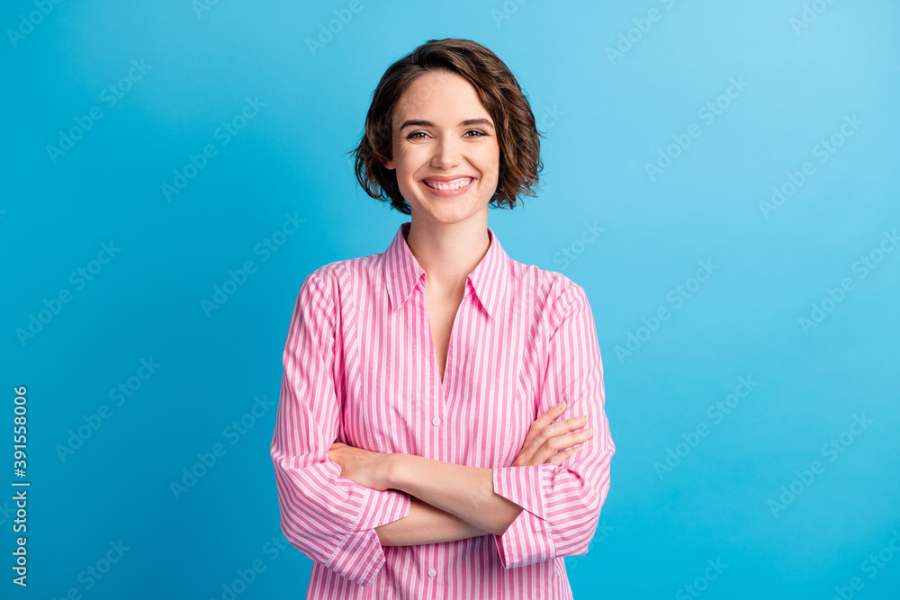 Fototapeta Photo portrait of curly charming pretty confident woman student dressed formal pink shirt arms crossed isolated blue color background