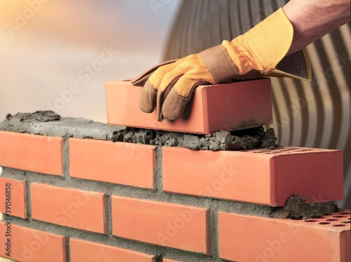 Fototapeta Bricklayer build cement masonry layer