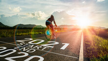 New Year 2021 Or Start Straight And Beginning Concept.Blurry Man Ride On Bike And Word 2021 Start Written On The Road At Sunset Add Lens Flare.Concept Of Challenge Or Career Path,business Strategy.