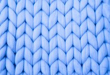 Knitted Background. Knitted Fabric Made Of Light Blue Merino Wool. Large Weave. Pattern Of Pigtails.